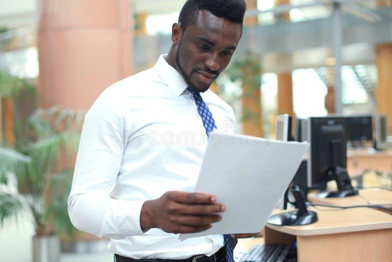 Riuscita carta afroamericana della lettura dell'uomo d'affari nel luogo di lavoro, esaminando documento finanziario, tenente caff fotografia stock