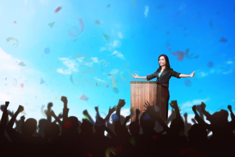 Riuscita donna asiatica di affari che dà un discorso davanti al immagini stock