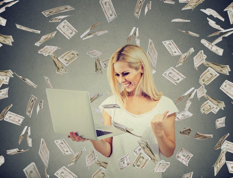Riuscita donna che per mezzo del computer portatile che sviluppa affare online che fa le banconote in dollari dei soldi che cadon fotografia stock