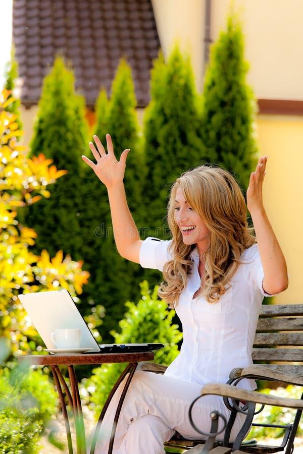Riuscita Donna Con Un Computer Portatile Nel Giardino Fotografia Stock