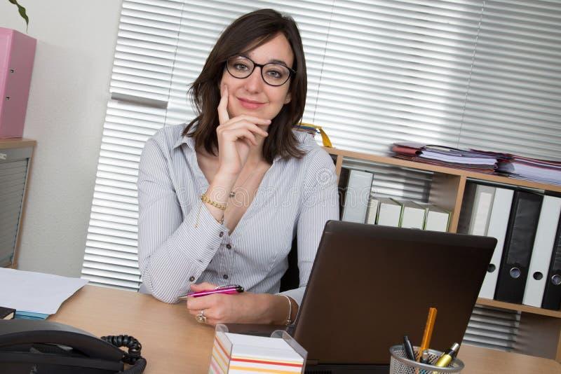 Riuscita donna di affari che lavora all'ufficio che esamina macchina fotografica fotografia stock