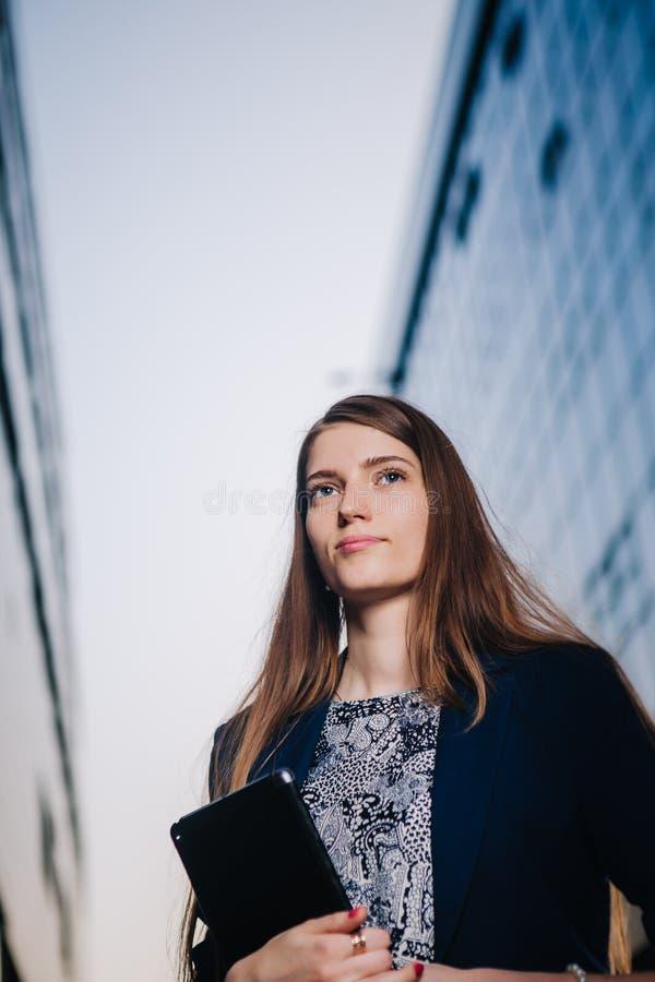 Riuscita donna di affari o imprenditore che prende le note e che parla sul cellulare mentre camminare all'aperto Funzionamento de fotografia stock
