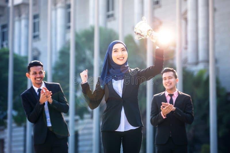 Riuscita donna musulmana di affari con le armi sulla tenuta del trofeo e sulla celebrazione, con i compagni di squadra che sosten immagine stock