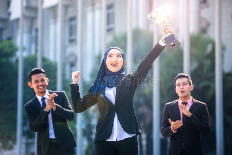 Riuscita donna musulmana di affari con le armi sulla tenuta del trofeo e sulla celebrazione, con i compagni di squadra che sosten fotografia stock libera da diritti