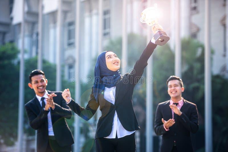 Riuscita donna musulmana di affari con le armi sulla tenuta del trofeo e sulla celebrazione, con i compagni di squadra che sosten immagini stock libere da diritti