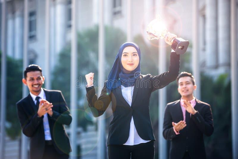 Riuscita donna musulmana di affari con le armi sulla tenuta del trofeo e sulla celebrazione, con i compagni di squadra che sosten fotografia stock