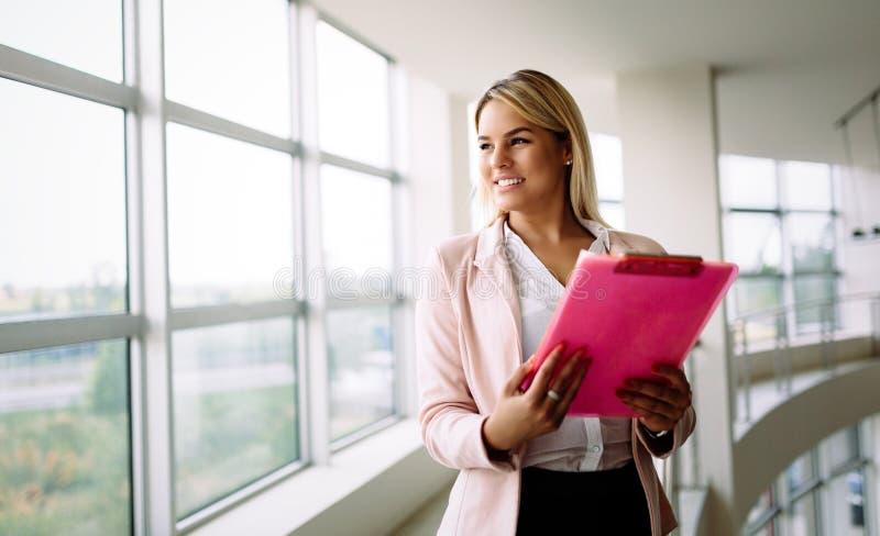 Riuscita donna sorridente ai documenti della tenuta del lavoro, finestra vicina stante di affari in ufficio fotografie stock libere da diritti