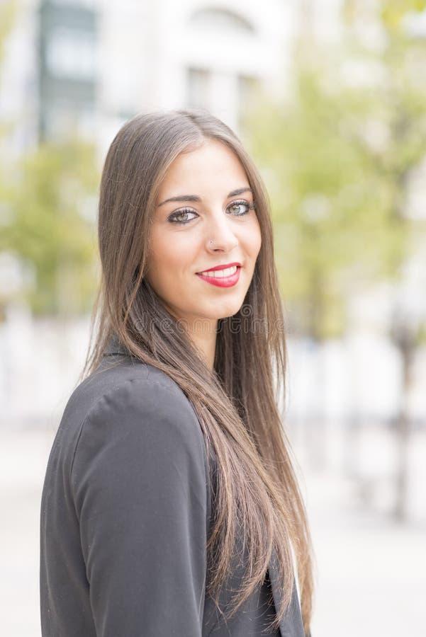 Riuscita donna sorridente di affari che esamina macchina fotografica nella via fotografia stock libera da diritti