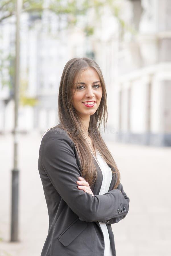 Riuscita donna sorridente di affari che esamina macchina fotografica nella via fotografie stock libere da diritti