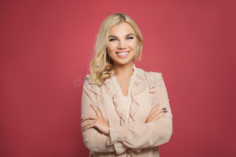 Riuscita donna sorridente su fondo rosa variopinto Ragazza bionda con le armi attraversate ed il sorriso grazioso fotografia stock