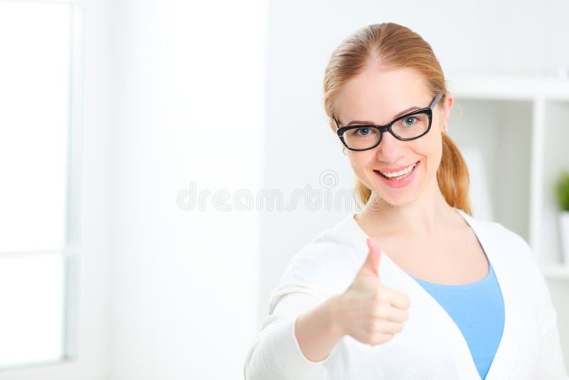 Riuscita donna in vetri che mostrano i pollici su fotografia stock libera da diritti
