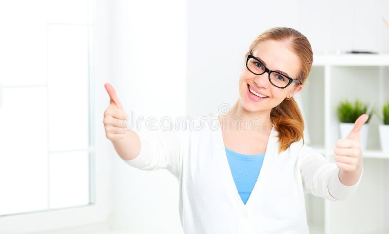 Riuscita donna in vetri che mostrano i pollici su fotografia stock
