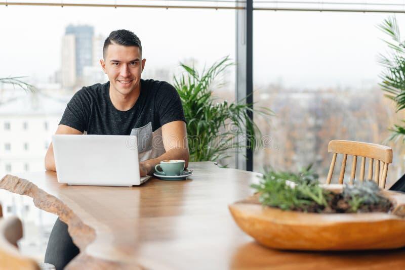 Riuscita gente, uomo d'affari in caff? comodo Lavoro delle free lance su netbook nel coworking moderno Bere del giovane immagini stock libere da diritti
