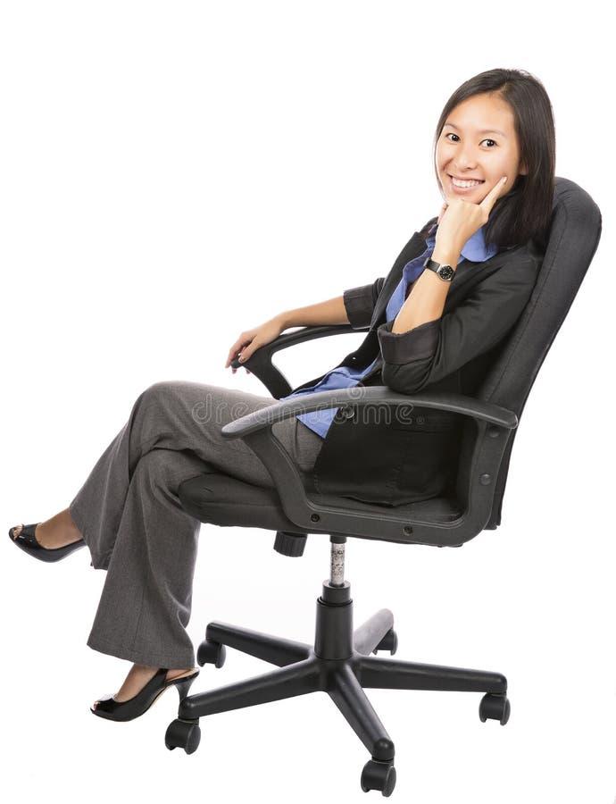 Riuscita giovane donna di affari sulla sedia sopra bianco fotografia stock libera da diritti