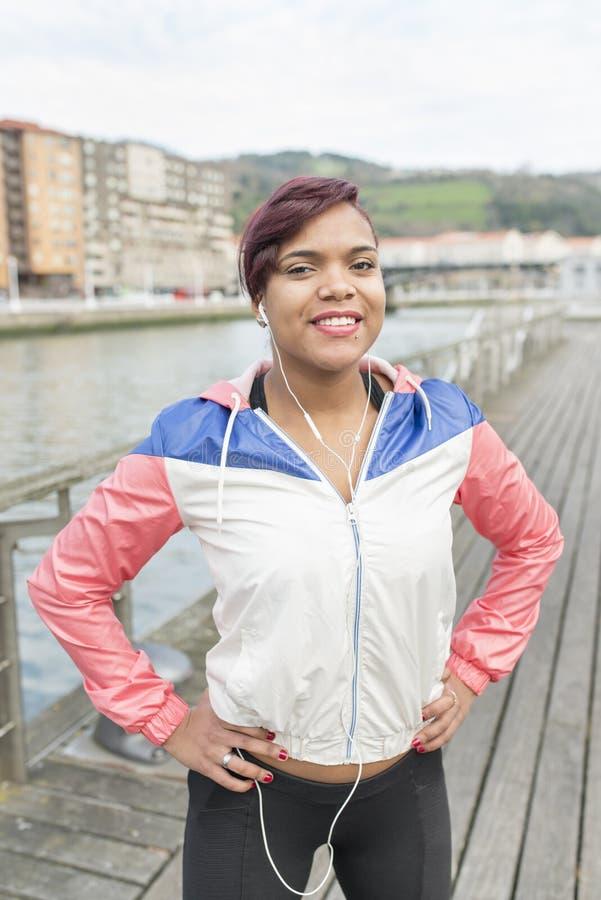 Riuscita giovane donna sorridente di sport con i headhones e lo Smart Phone fotografia stock libera da diritti