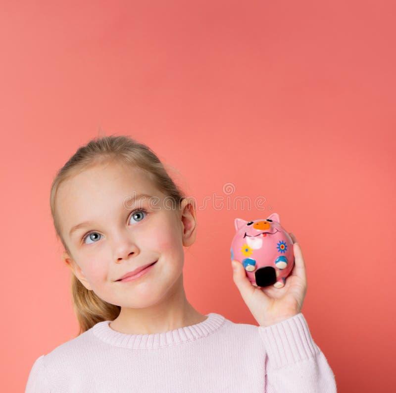 Riuscita ragazza sorridente quinta nel porcellino salvadanaio della tenuta del maglione sulla palma isolata sopra fondo e cercare fotografia stock