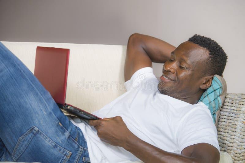 Riuscita rete afroamericana nera attraente e felice dell'uomo con il computer portatile a sorridere dello strato del salone alleg immagini stock libere da diritti