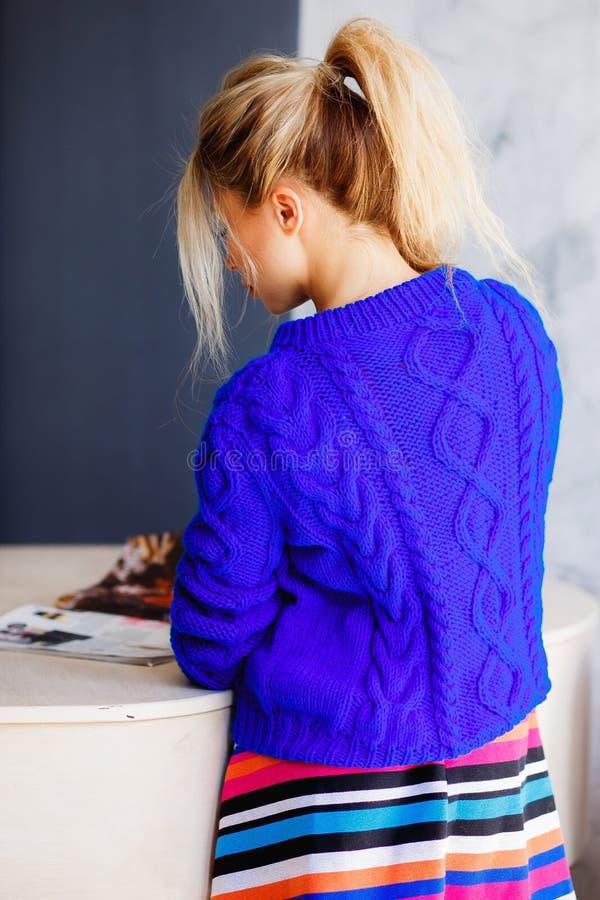 Riuscita signora di affari Bella giovane donna che tiene una rivista corporativa e che sorride mentre pendendo al contatore della immagine stock libera da diritti