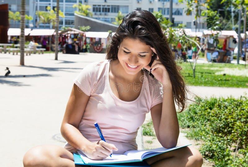 Riuscita studentessa caucasica che impara all'aperto fotografia stock libera da diritti