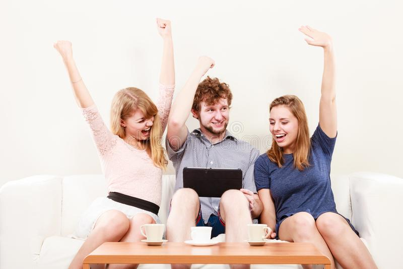 Riusciti amici felici con la compressa a casa immagine stock libera da diritti