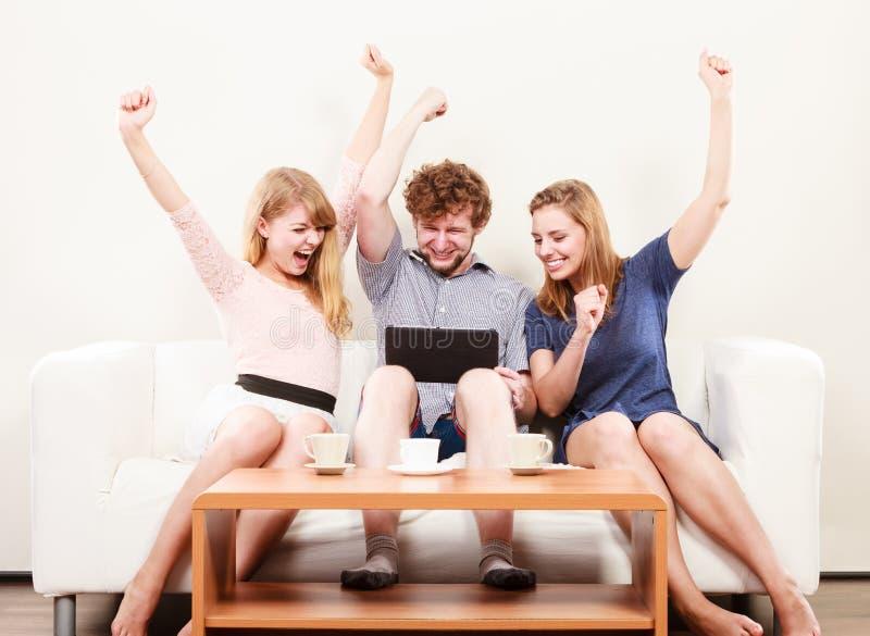 Riusciti amici felici con la compressa a casa fotografie stock