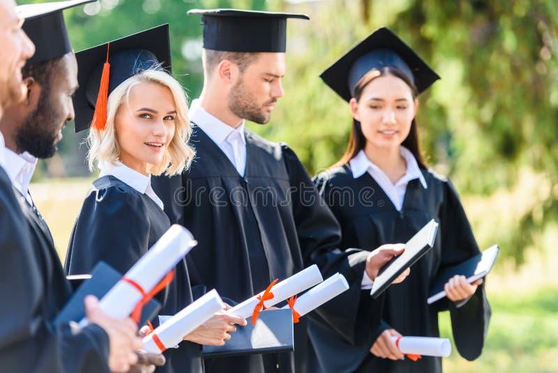 riusciti studenti graduati in capi e nella tenuta dei cappelli fotografia stock