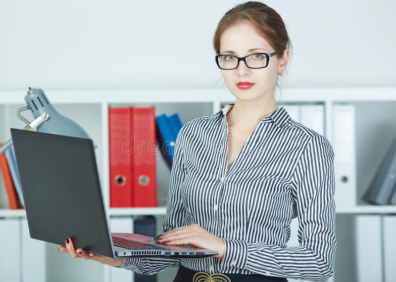 Riuscito computer portatile della tenuta della giovane donna in mani che guardano in camera immagine stock