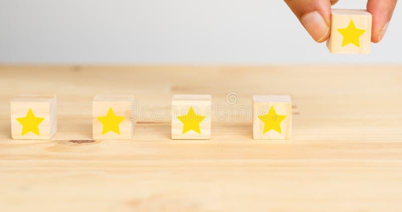 Riuscito concetto di affari, prova dell'uomo della mano per mettere la quinta stella per completare stella cinque che valuta all' immagine stock