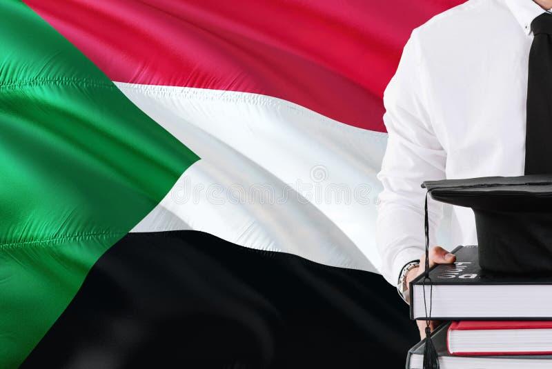Riuscito concetto sudanese di istruzione dello studente Tenuta i libri e del cappuccio di graduazione sopra il fondo della bandie fotografie stock