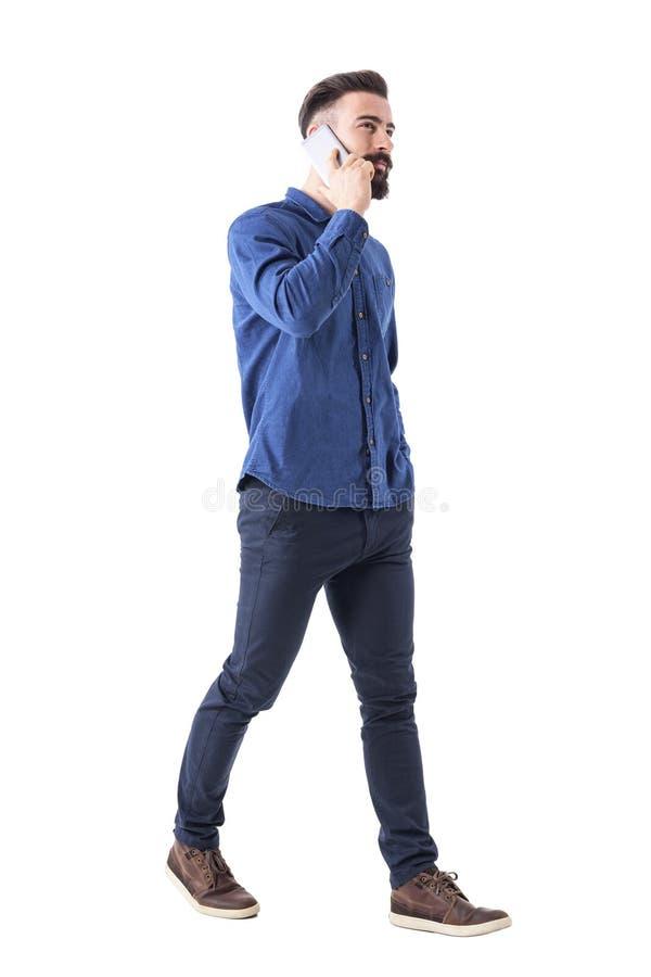Riuscito giovane ceo maschio alla moda che cammina e che parla sul cercare del telefono cellulare immagini stock