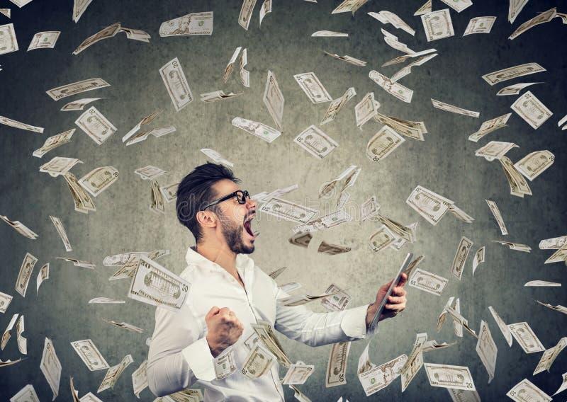 Riuscito giovane che per mezzo della compressa che costruisce i soldi online dei guadagni di affari immagini stock libere da diritti