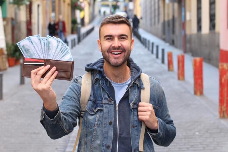 Riuscito giovane tipo con il portafoglio pieno all'aperto immagini stock libere da diritti