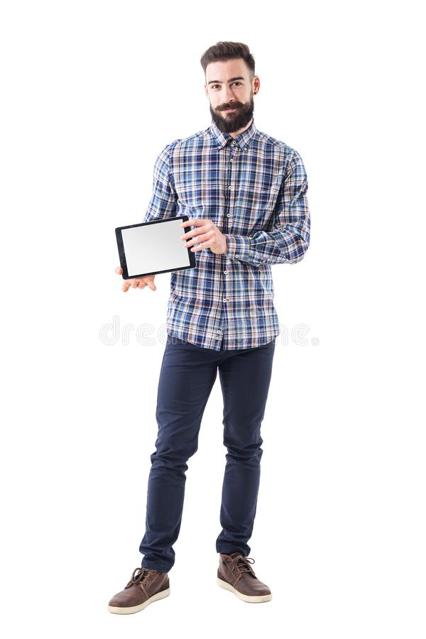 Riuscito giovane uomo barbuto sicuro felice di affari che mostra lo schermo in bianco della compressa alla macchina fotografica fotografia stock libera da diritti