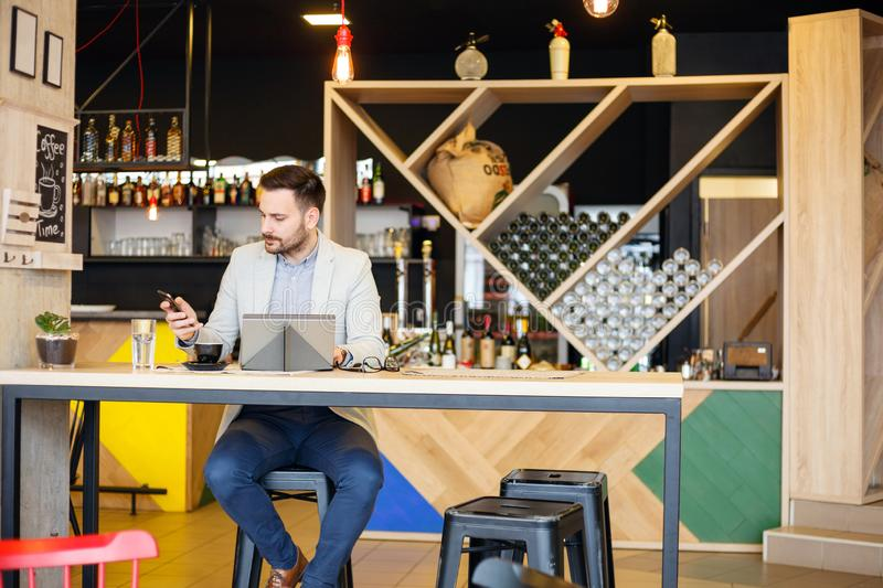 Riuscito giovane uomo d'affari che lavora in un caffè moderno fotografia stock libera da diritti