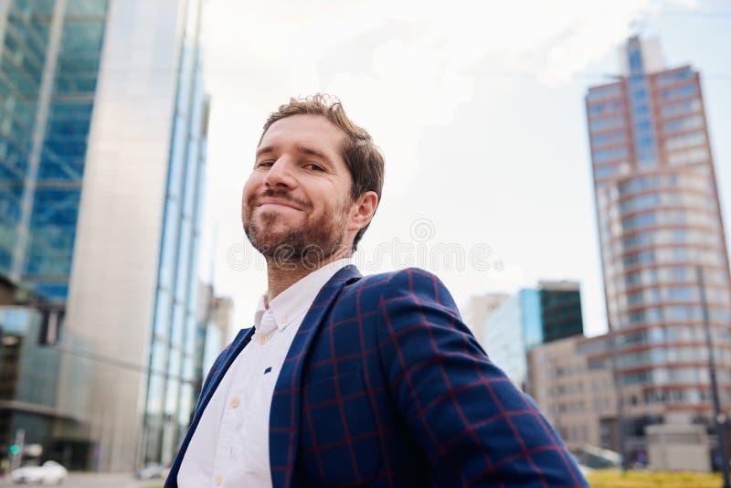 Riuscito giovane uomo d'affari che sorride con confidenza mentre stando nella città immagini stock libere da diritti