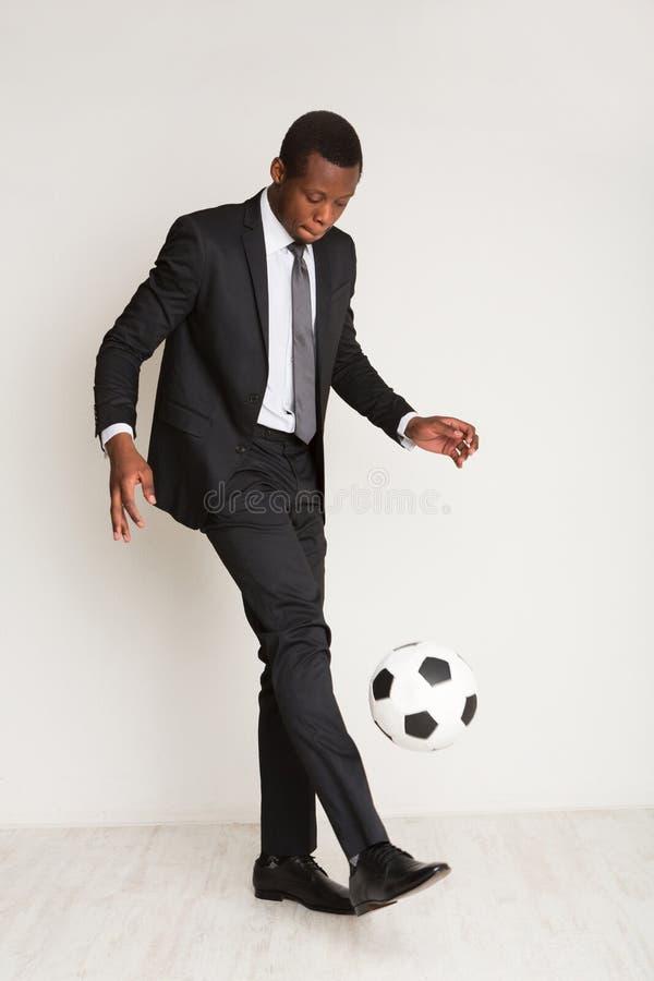 Riuscito giovane uomo d'affari nero in vestito, legame che gioca palla fotografia stock