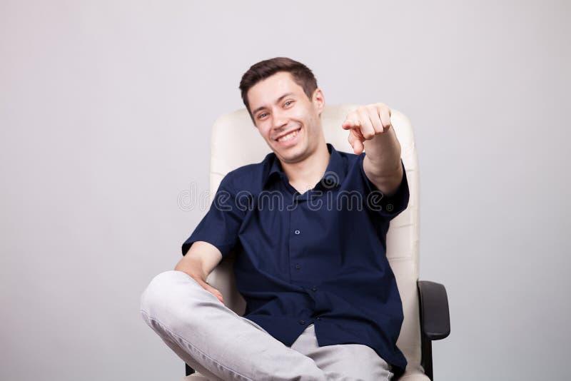 Riuscito giovane uomo d'affari sorridente felice in camicia blu casuale che si siede su una sedia dell'ufficio fotografia stock libera da diritti
