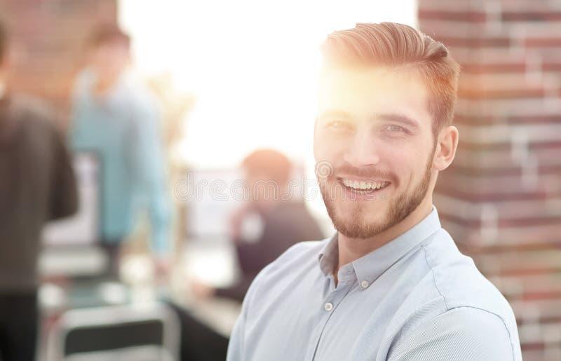 Riuscito giovane uomo di affari che sta con i suoi colleghi in b immagini stock
