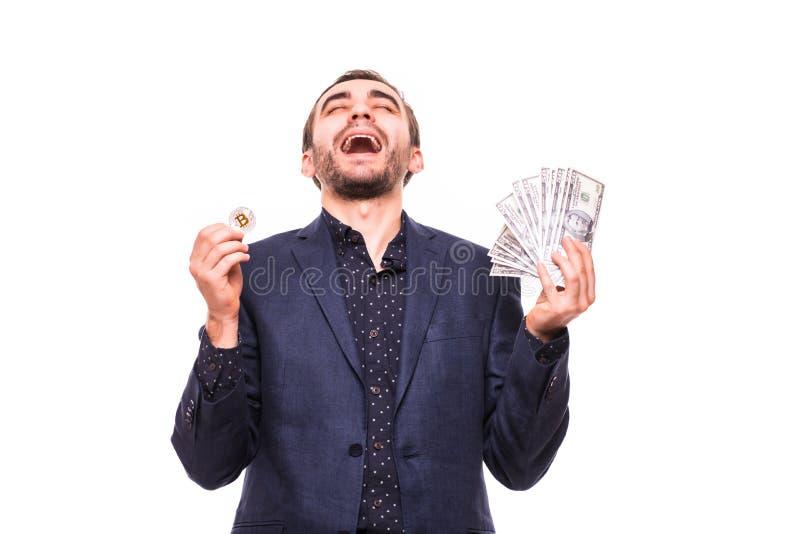 Riuscito grido felice bello emozionante felice dell'uomo di affari con bitcoin nei dollari della mano e dei contanti di ona in al fotografie stock