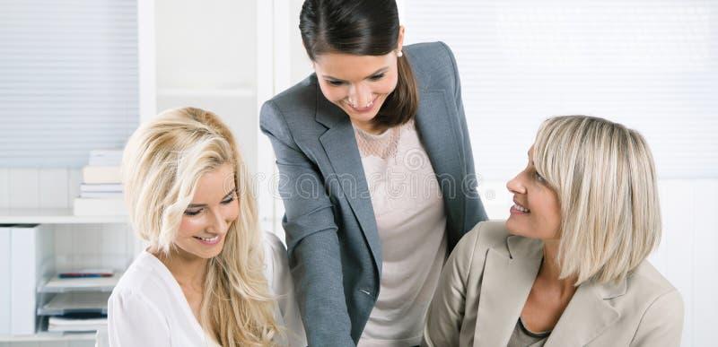 Riuscito gruppo della donna di affari istruita che si siede allo scrittorio w immagine stock