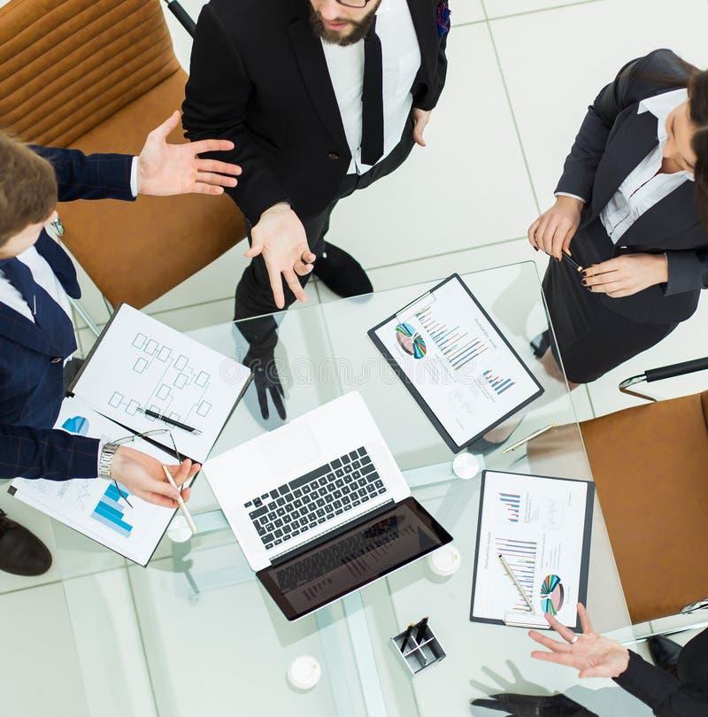 Riuscito gruppo di affari che discute commercializzando i grafici ad una riunione di lavoro immagini stock libere da diritti