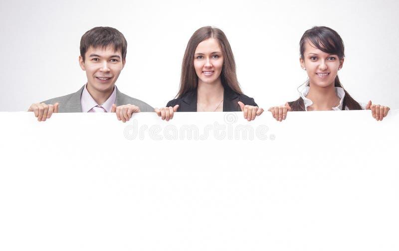 Riuscito gruppo di affari che tiene un'insegna in bianco immagini stock libere da diritti