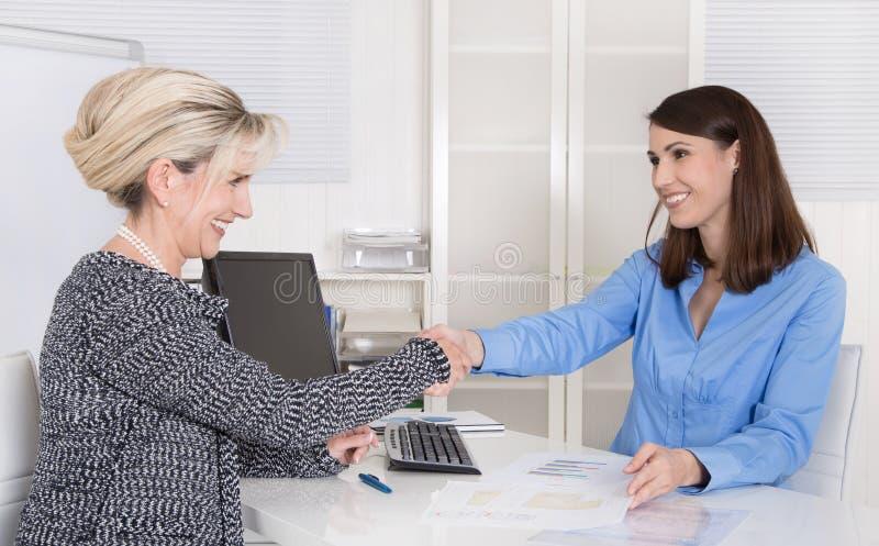 Riuscito gruppo o stretta di mano di affari della donna in un'intervista di lavoro fotografia stock libera da diritti