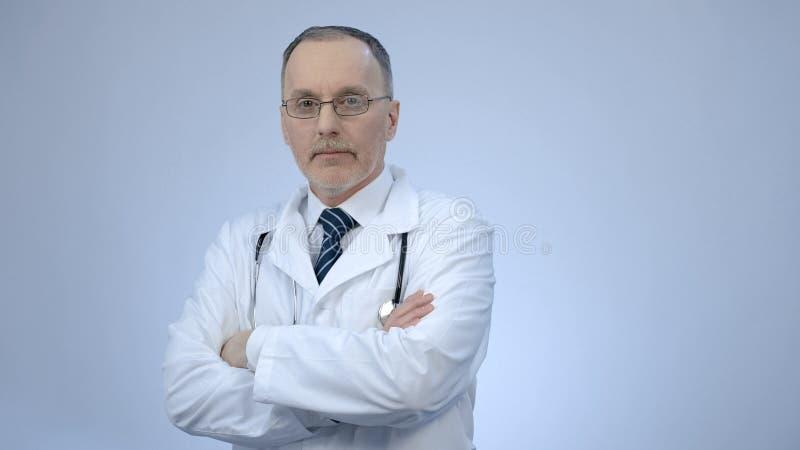 Riuscito medico sicuro che esamina macchina fotografica con le armi piegate, servizi della clinica immagine stock
