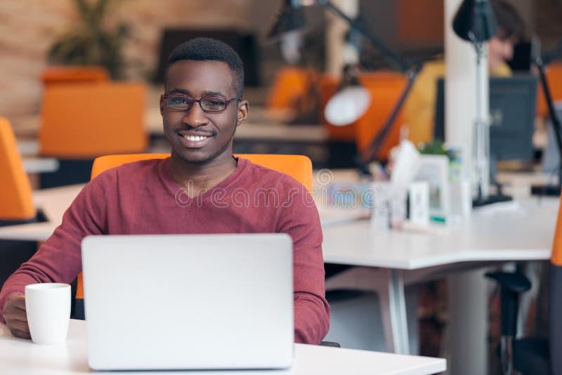 Riuscito uomo afroamericano sorridente bello che per mezzo del computer portatile fotografia stock