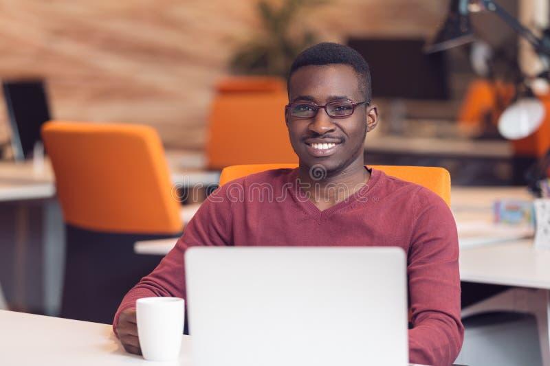 Riuscito uomo afroamericano sorridente bello che per mezzo del computer portatile fotografia stock libera da diritti