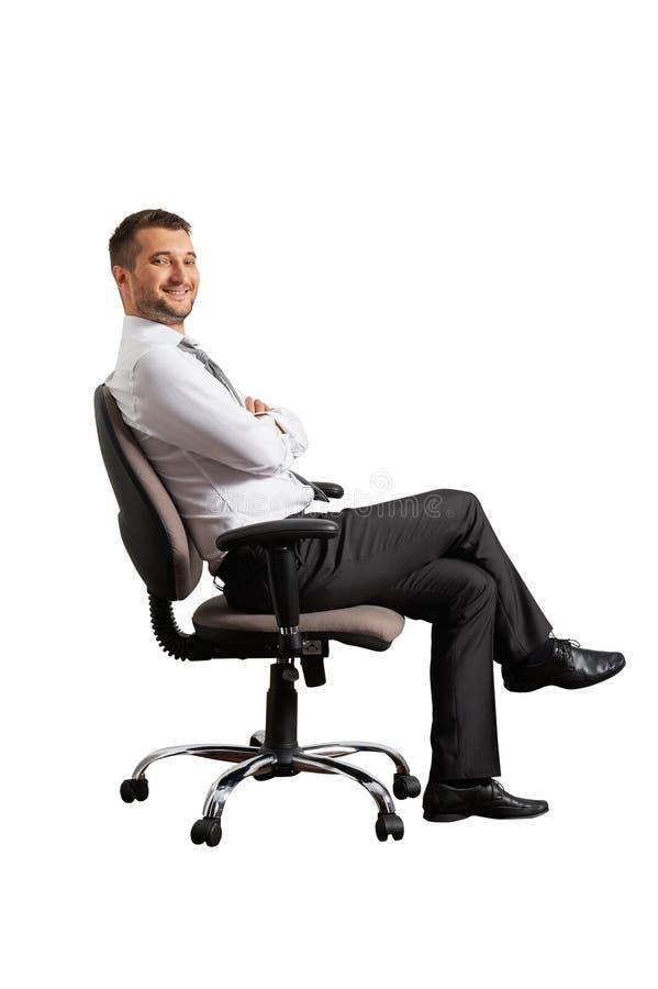 Riuscito uomo che si siede sulla sedia dell'ufficio fotografie stock libere da diritti