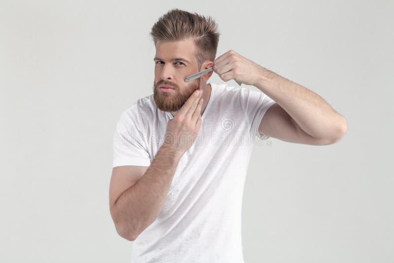 Riuscito uomo con la barba fertile dello zenzero punga sulle latte sulla barba che esamina la macchina fotografica Vestito in abb immagine stock libera da diritti