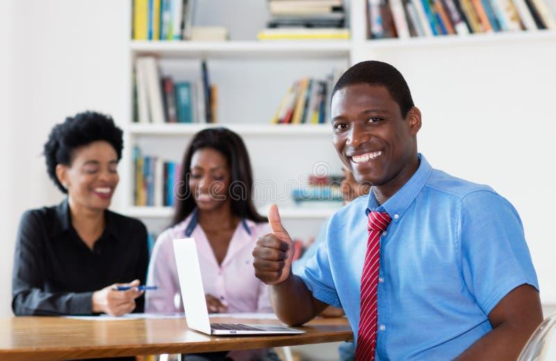Riuscito uomo d'affari afroamericano con il gruppo ed il computer fotografie stock