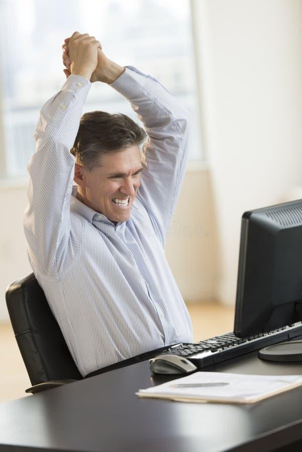 Riuscito uomo d'affari With Arms Raised che per mezzo del computer immagini stock